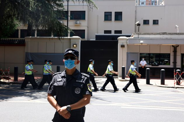 Chinese police officers march past the former U.S. Consulate in Chengdu on
