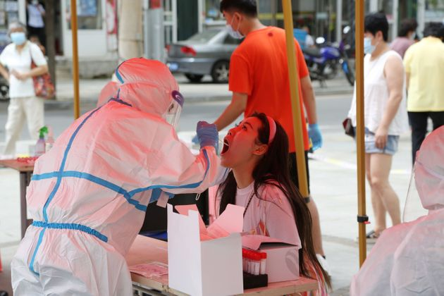 A health worker carries out a COVID-19 coronavirus test at a makeshift testing center in Dalian, in China's...
