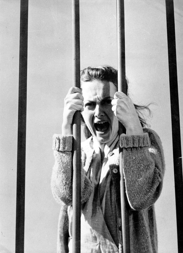 1948: British actress Olivia De Havilland clutches the bars of her cell in the film 'The Snake Pit',...