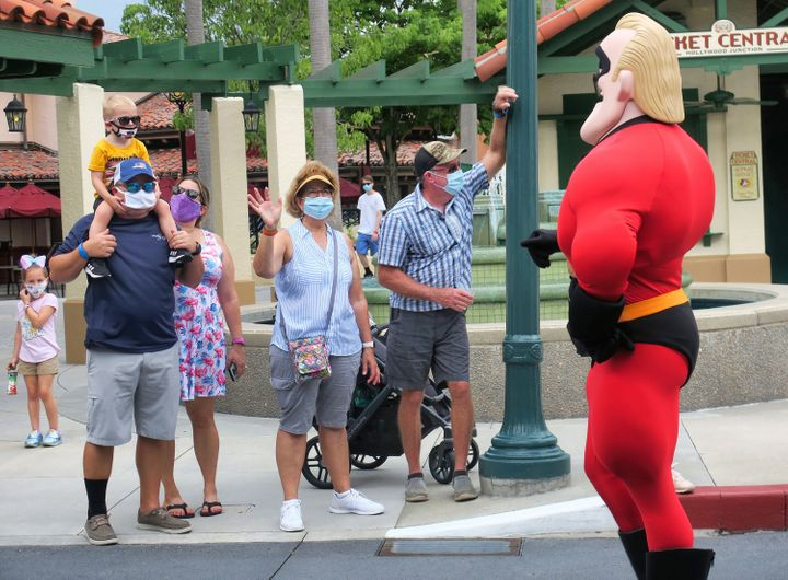 Guests wave to Mr. Incredible during a pop-up appearance of Pixar characters at Disney's Hollywood Studios at Walt Disney World on July 16, the second day of the park's reopening, in Lake Buena Vista, Florida.