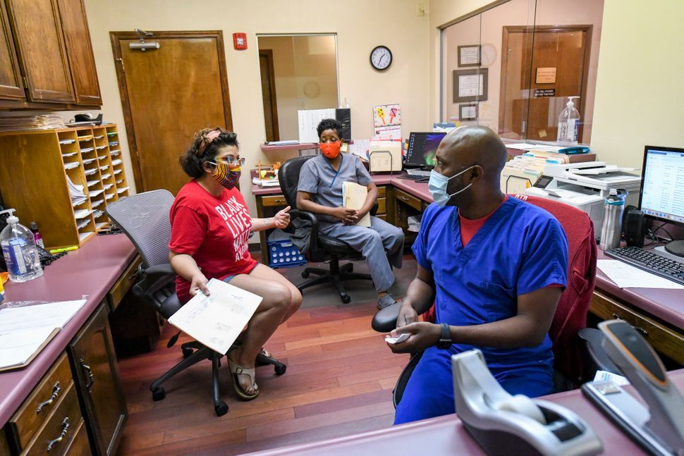 Amanda Reyes, center, talks with medical team manager Alesia Horton, left, and office manager Chadric Jackson in the front of