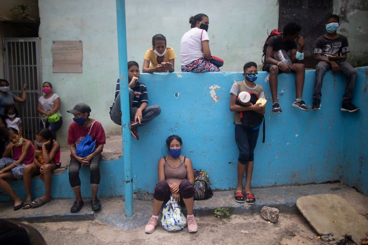 Residents wearing protective face masks wait outside a soup kitchen to receive pack-and-go lunches in the Petare neighborhood of Caracas, Venezuela, Wednesday, July 15, 2020, amid the new coronavirus pandemic.