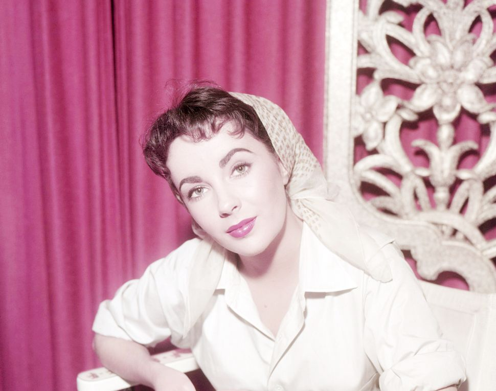 Η διάσημη ηθοποιός Ελίζαμπεθ Τέιλορ κάθεται στην καρέκλα του σκηνοθέτη και φοράει μαντήλι, το 1955.