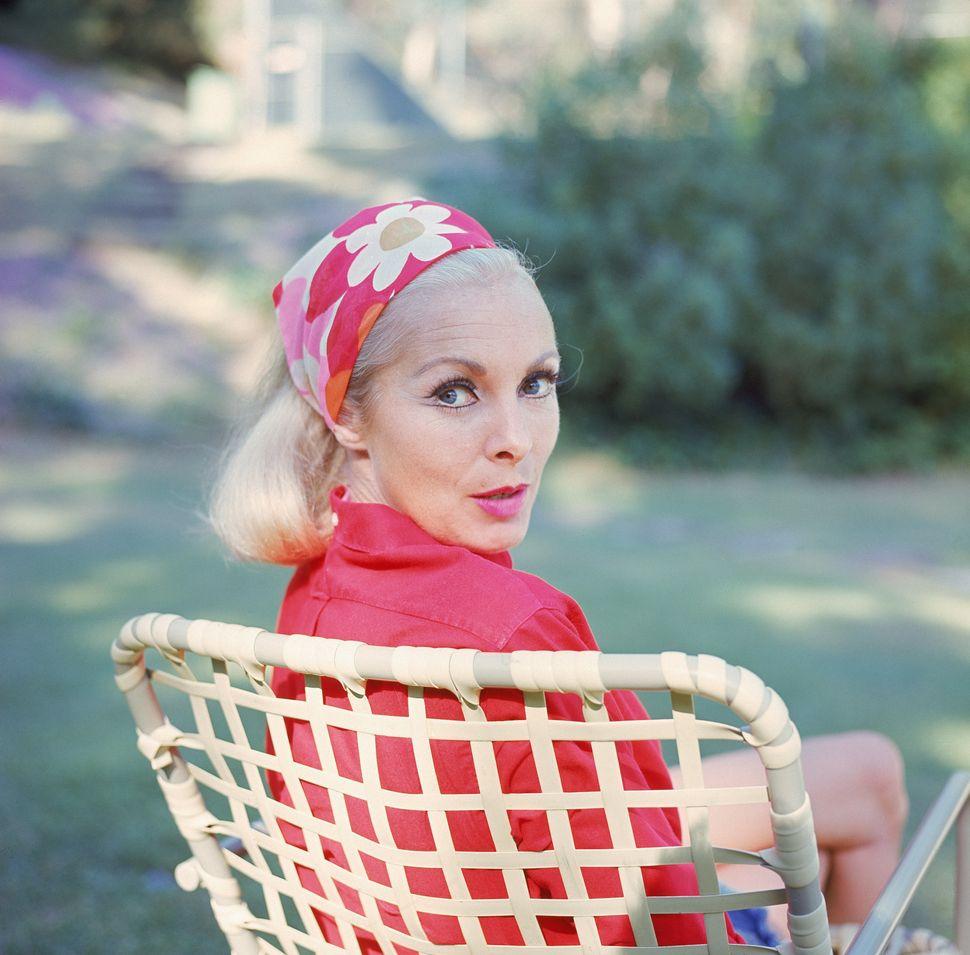Η Αμερικανίδα ηθοποιός Τζάνετ Λι κάθεται στην καρέκλα φορώντας ένα κόκκινο, λουλουδάτο μαντήλι που ταιριάζει με το πουκάμισο, στα τέλη της δεκαετίας του '60.