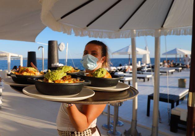 Una camarera con mascarilla lleva platos a una mesa en el bar Purobeach en Cala Estancia, en