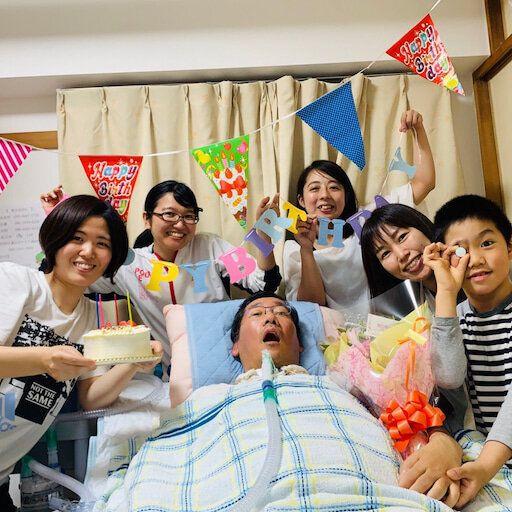 家族や訪問介護のスタッフらと49歳の誕生日を祝う太田守武さん(中央)