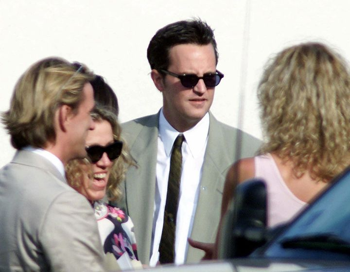 Matthew Perry talks with unidentified guests at the oceanside wedding of Brad Pitt and Jennifer Aniston in Malibu, Calif., Saturday, July 29, 2000