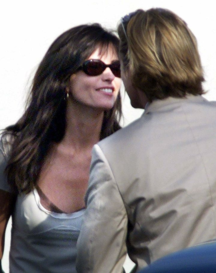 Courteney Cox greets a friend before boarding a shuttle for the oceanside wedding of Brad Pitt and Jennifer Aniston