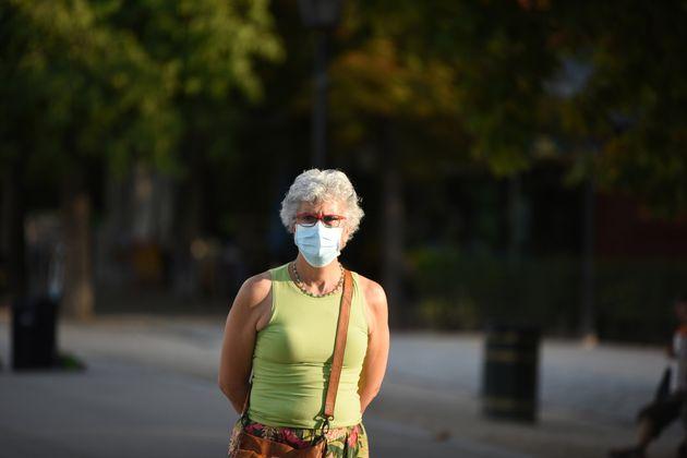 Una mujer pasea con mascarilla por el Parque de El Retiro, en