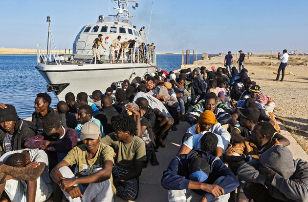 TOPSHOT - This picture taken on October 1, 2019 shows rescued migrants sitting on a pier next to a Libyan...