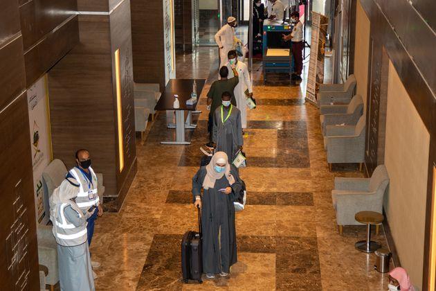 Des voyageurs se font vérifier leur température à leur arrivée à l'hôtel,...