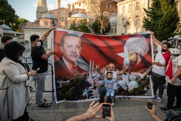 Un homme et un petit garçon sont pris en photo devant une affiche représentant le président...