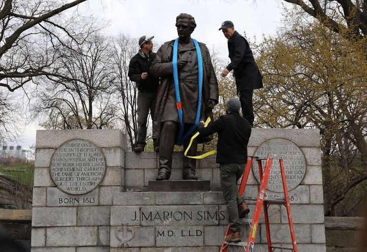 Parks Department workers place a harness over a statue of James Marion Sims before it is taken down from its pedestal at Central Park and East 103rd Street on April 17, 2018 in New York City.