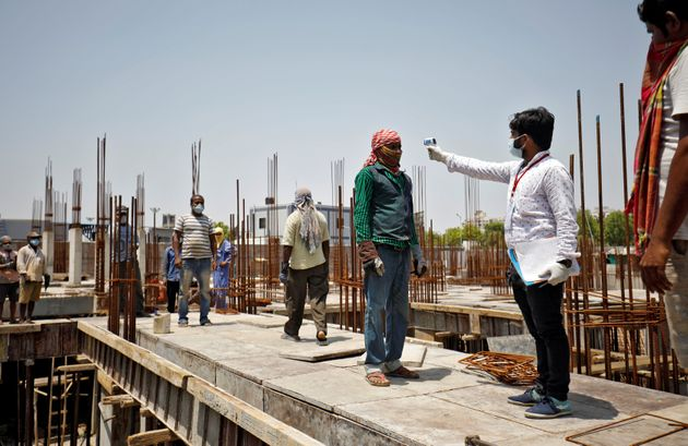 A health worker uses an infrared thermometer to measure the temperature of a labourer at the construction...