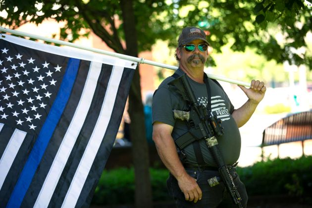 Josh Bradley holds a thin blue line flag in in Vancouver, Wa., on June 26, 2020, during a rally against...