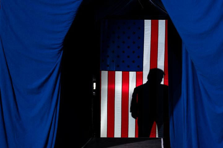 The shadow of President Donald Trump falls on a flag during a Feb. 20 campaign rally in Colorado Springs, Colorado.