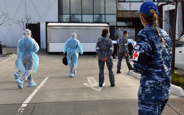 Australian Defence Force personnel escort their staff into the Epping Gardens aged care facility in the Melbourne suburb of Epping on July 28, 2020 as the city battles fresh outbreaks of the COVID-19 coronavirus.