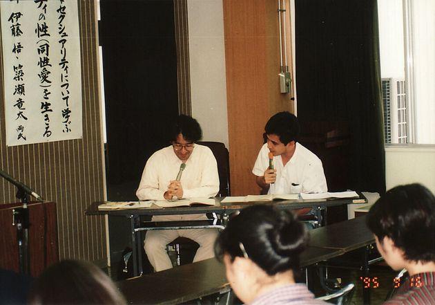 講演中の伊藤悟さん(左)と簗瀬竜太さん。写真の下部に1995年と記されている。
