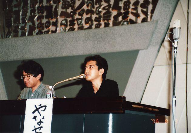 講演活動をする伊藤悟さん(左)と簗瀬竜太さん。1990年代後半の撮影。