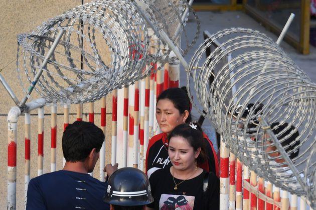 Deux femmes ouïgoures passant par l'entrée d'un bazar à Hotan, dans la région...