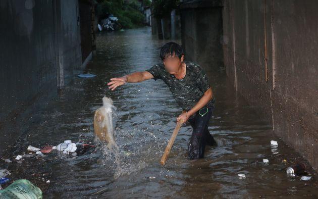 대전지역에 호우경보가 발효된 30일 오전 대전 동구 대동 주택가에서 시민이 하수구를 막고 있는 쓰레기를 치우고