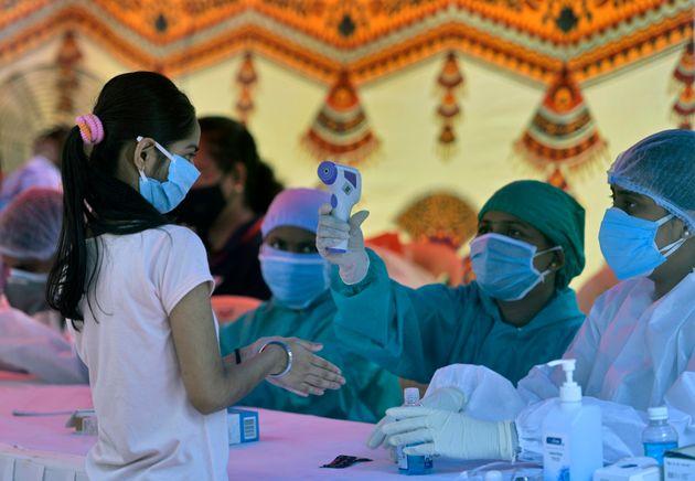 28일 뭄바이의 한 코로나바이러스 검사장에서 의료진이 한 시민의 체온을 확인하고