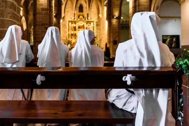 Valencia, Spain - September 25, 2019: Group of Christian nuns with white robes praying in a