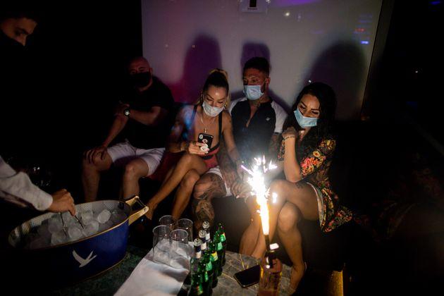 Varios jóvenes, juntos y con mascarillas en una discoteca, uno de los focos de rebrotes en las...
