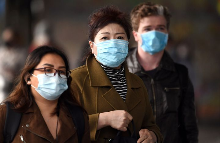 Commuters walk outside Melbourne's Flinders Street Station on July 23, on the first day of the mandatory wearing of face masks in public areas.