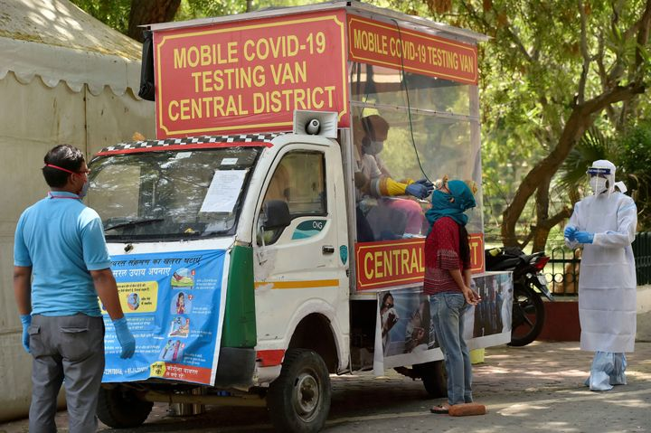 A health official collects a sample from a medical staff of a hospital from a mobile Covid-19 testing van onApril 30, 2