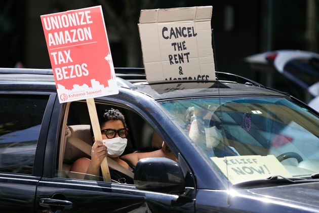 People drive around the block with anti-Jeff Bezos signs as they participate in a
