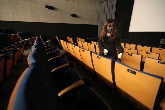 営業再開後、感染症対策のため、映画の上映終了後に座席の手すりを消毒する映画館の従業員(6月1日)