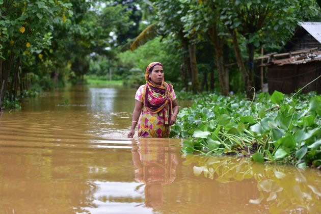 A woman wades through a flooded street in Nagaon district of Assam on 22 July