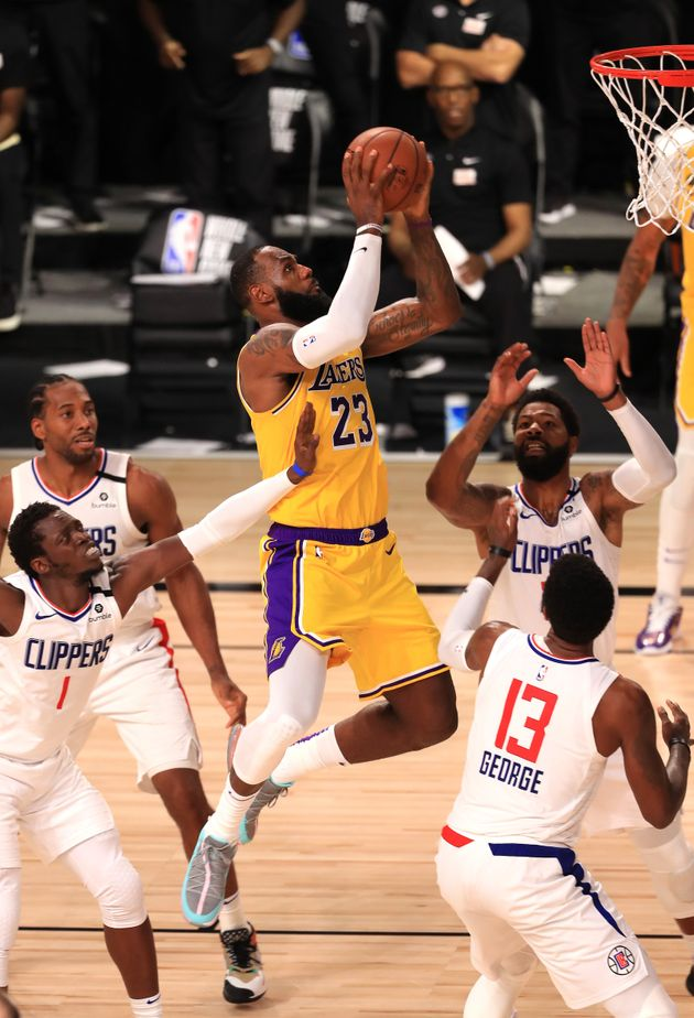 LAKE BUENA VISTA, FLORIDA - JULY 30: LeBron James #23 of the Los Angeles Lakers makes a shot against...
