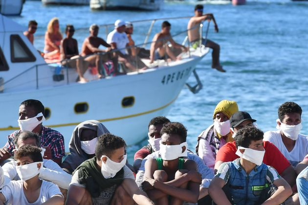 TOPSHOT - Migrants rescued by Italys' Guardia Costiera ( Coast Guard ) sits as a boat with tourists enter...