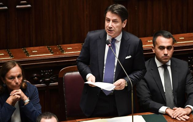 Italy's Prime Minister Giuseppe Conte (C) stands next to Italy's Interior Minister Luciana Lamorgese...