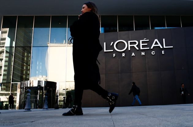 A woman walks by the logo of French cosmetics group L'Oreal in the western Paris suburb of Levallois-Perret,...