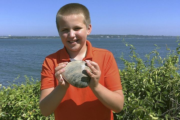 Cooper Monaco holds the large quahog he found Monday while clamming with his grandfather in Westerly, R.I. The quahog is more