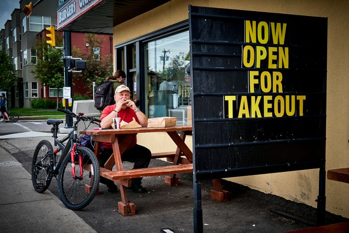 A patron enjoys takeout in Calgary, Alta., on June 23, 2020, amid a worldwide COVID-19 pandemic.