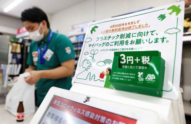 レジ袋が有料となり、コンビニのレジ近くには告知のパネルが設置された=2020年7月1日午前、東京都港区、池田良撮影