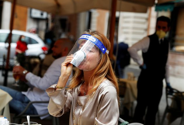 A woman wearing a face shield drinks coffee at a cafe as Italy eases some of the lockdown measures put...