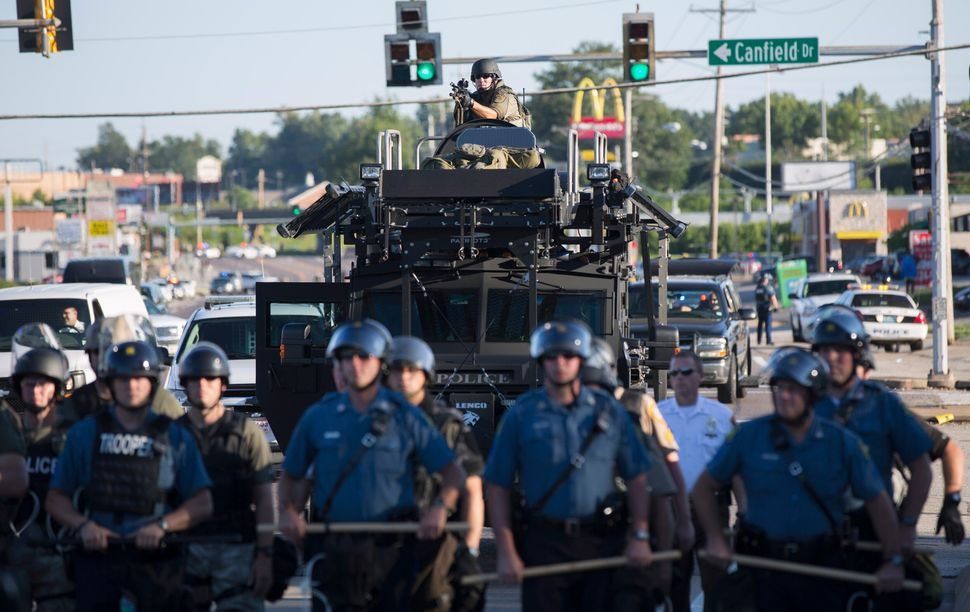 Riot police stand guard as demonstrators protest the shooting death of teenager Michael Brown in Ferguson, Missouri August 13