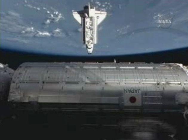 ドッキングのため国際宇宙ステーション(ISS)に接近する米スペースシャトル「エンデバー」。下は日本実験棟「きぼう」(2009年7月撮影)。[米航空宇宙局(NASA)テレビから]