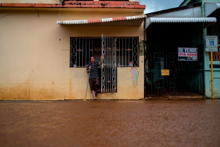 A man looks on from the front of his house after Tropical Storm Isaias affected the area in Mayaguez, Puerto Rico on July 30,