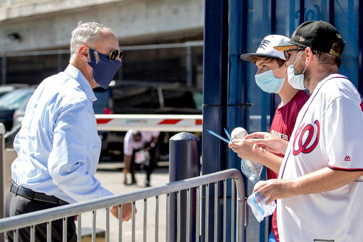MLB Commissioner Rob Manfred, left, speaks with fans as he arrives at Nationals Park for the New York Yankees and the Washing