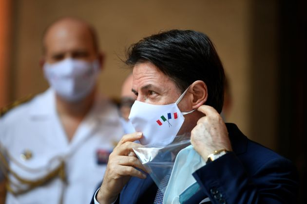 Italian Prime Minister Giuseppe Conte wearing a face mask is seen during a handover ceremony of the piece...