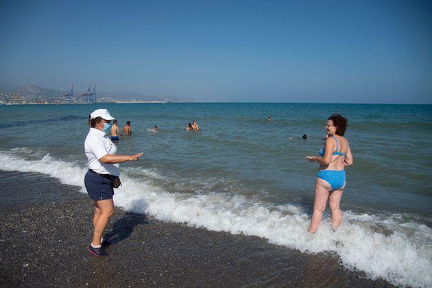 Personal del 112 de Málaga solicitando a una bañista que se ponga la
