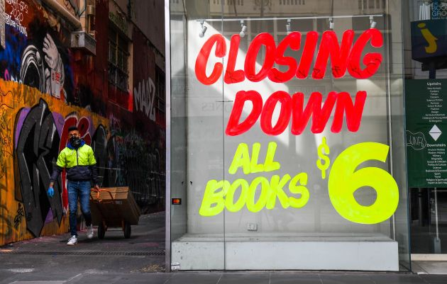 A worker walks past a empty shop in Melbournes central business district on August 3, 2020 after the...