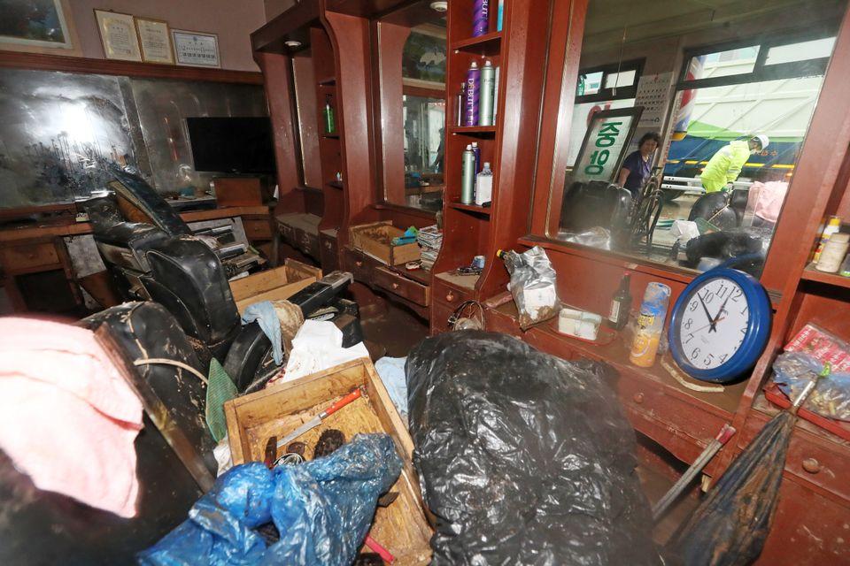 3일 오후 경기도 안성시 죽산시외버스터미널 인근 이발소에서 주인이 밀려온 토사에 못쓰게 된 생활용품을 정리하고
