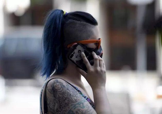 Una mujer con mascarilla habla por teléfono, en Madrid (España) a 30 de julio de